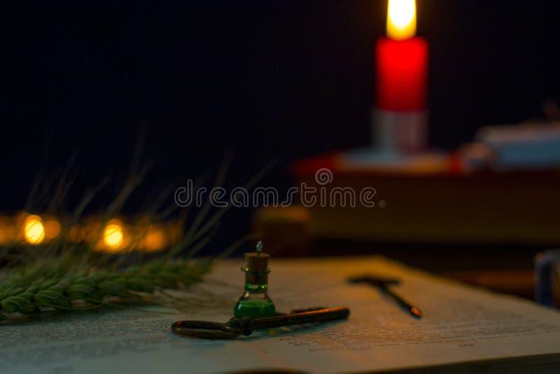 Μαγική φίλτρο, αρχαία βιβλία και κεριά στο σκοτεινό υπόβαθρο στοκ φωτογραφίες