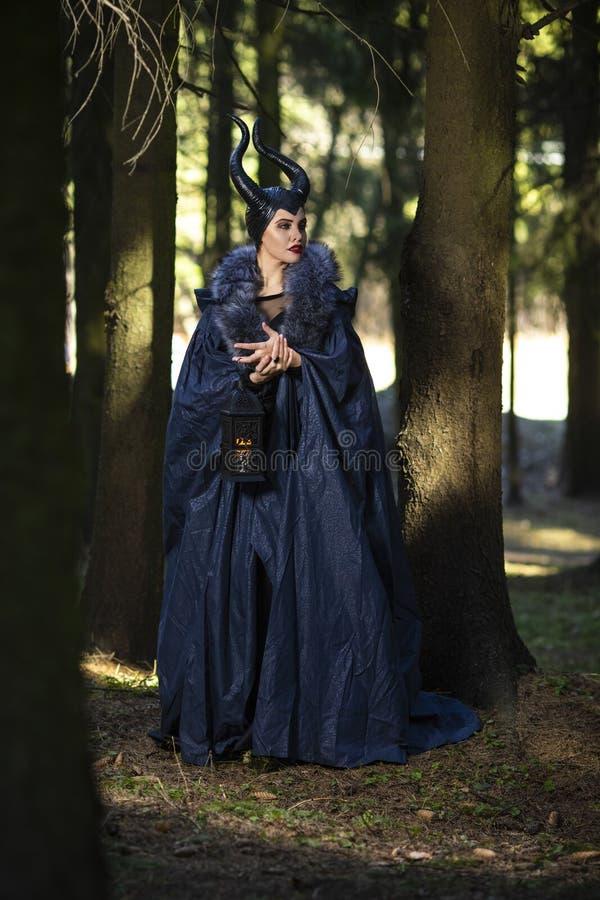 Μαγικός επιβλαβής λαμπτήρας ιματισμού γυναικών και δασικός εκμετάλλευσης κέρατων την άνοιξη υπό εξέταση στοκ φωτογραφία