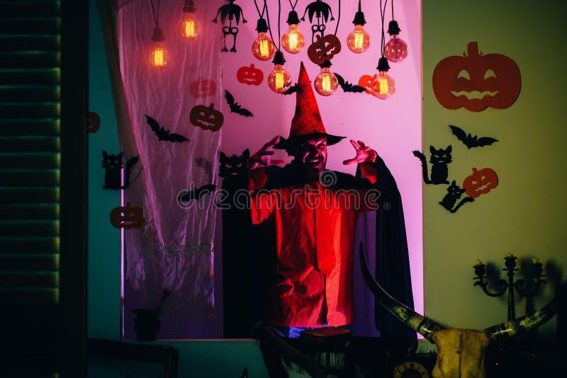 Μαγικός, enchantment, witchcraft Το τρομακτικό άτομο προσώπου με τη φρίκη αποτελεί το κράτημα της κολοκύθας επικεφαλής φανάρι γρύ στοκ εικόνα με δικαίωμα ελεύθερης χρήσης