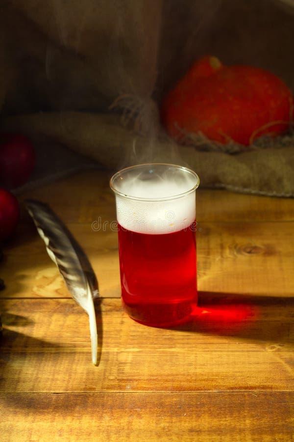 Μαγικό εργαστήριο μαγισσών με την κόκκινη φίλτρο για το ξύλινο υπόβαθρο αποκριών στοκ φωτογραφία με δικαίωμα ελεύθερης χρήσης