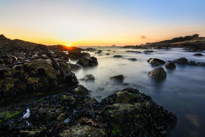 Μαγικό και πορτοκαλί ηλιοβασίλεμα σε μια δύσκολη παραλία στο Πόρτο, Πορτογαλία, Ευρώπη Μακρύ πλάνο έκθεσης στοκ φωτογραφία με δικαίωμα ελεύθερης χρήσης