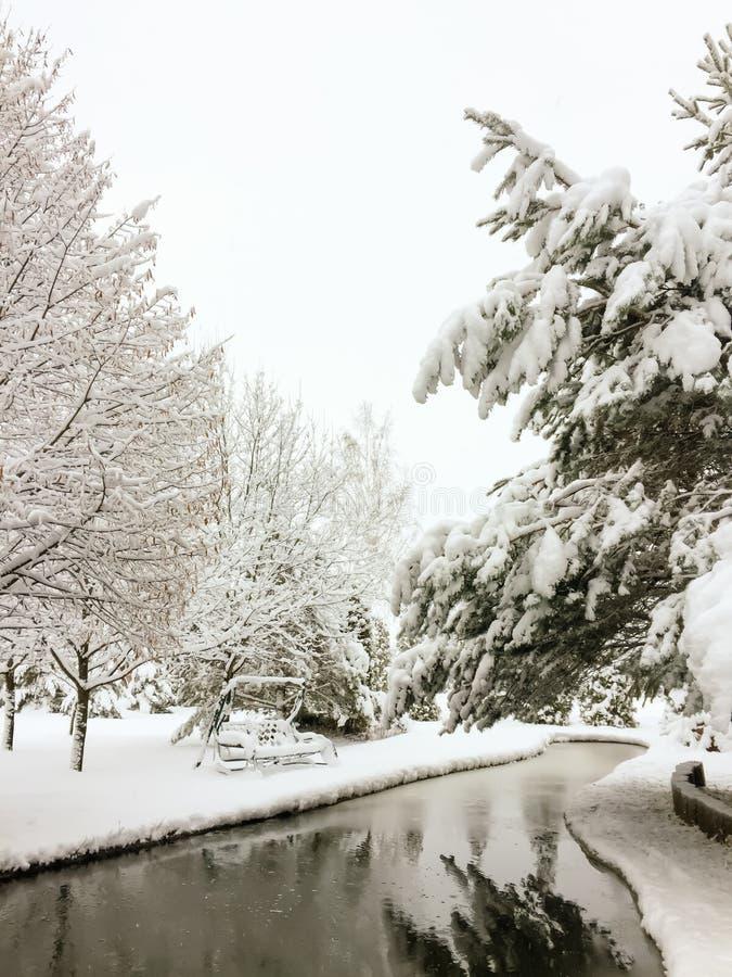 Μαγικό χειμερινό τοπίο σε ένα πάρκο με μια ταλάντευση λιμνών και κήπων που καλύπτεται με το πρώτο χνουδωτό χιόνι στοκ εικόνες