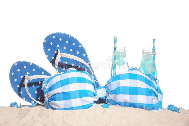 Μαγιό, σαγιονάρες και κρύα ποτά στην άμμο στο άσπρο κλίμα στοκ εικόνες με δικαίωμα ελεύθερης χρήσης