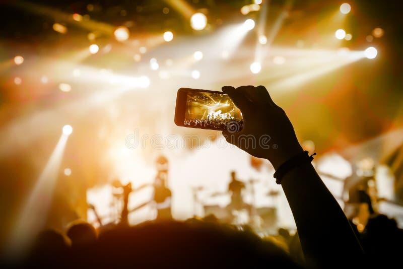 Μαγνητοσκόπηση μια συναυλία στην κινητή τηλεφωνική κάμερα, κίτρινο φως στοκ εικόνες με δικαίωμα ελεύθερης χρήσης