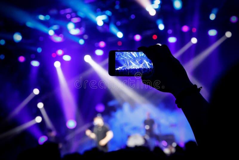 Μαγνητοσκόπηση μια συναυλία στην κινητή τηλεφωνική κάμερα, μπλε φως σκηνών στοκ φωτογραφίες με δικαίωμα ελεύθερης χρήσης