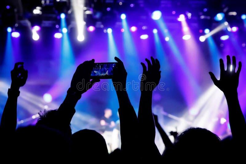 Μαγνητοσκόπηση μια συναυλία στην κινητή τηλεφωνική κάμερα, μπλε φως σκηνών στοκ εικόνες με δικαίωμα ελεύθερης χρήσης