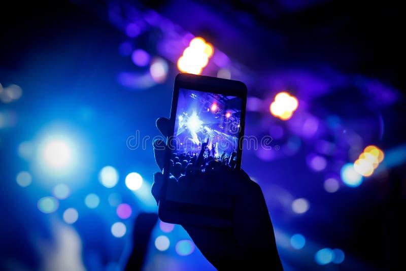 Μαγνητοσκόπηση μια συναυλία στην κινητή τηλεφωνική κάμερα στοκ εικόνα