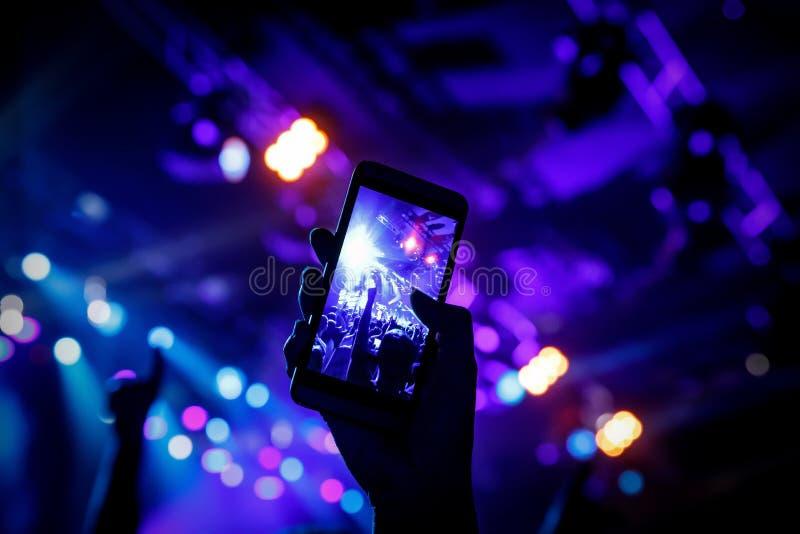 Μαγνητοσκόπηση μια συναυλία στην κινητή τηλεφωνική κάμερα, μπλε φως σκηνών στοκ φωτογραφίες
