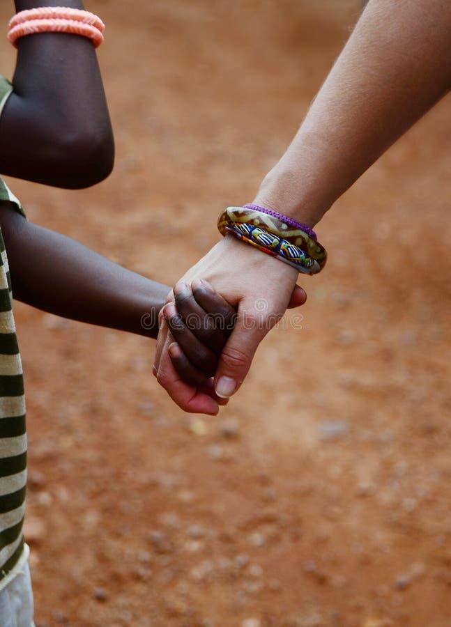 Μαζί για την Αφρική: Κρατώντας χέρια ανάμεσα στο φτωχό παιδί από την Αφρική και τη λευκή γυναίκα από τον Καύκασο στοκ φωτογραφίες