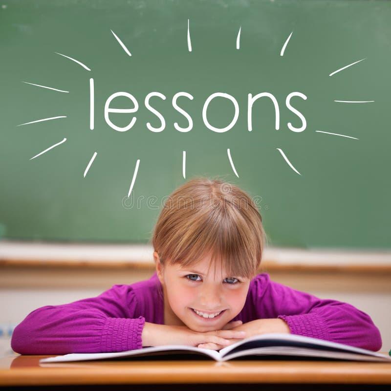 Μαθήματα ενάντια στη χαριτωμένη συνεδρίαση μαθητών στο γραφείο στοκ φωτογραφία