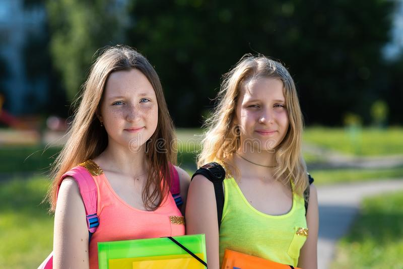 Μαθήτρια δύο κοριτσιών Καλοκαίρι στη φύση Στα χέρια του κρατά το φάκελλο των σημειωματάριων Πίσω από τα σακίδια πλάτης του Έννοια στοκ φωτογραφίες