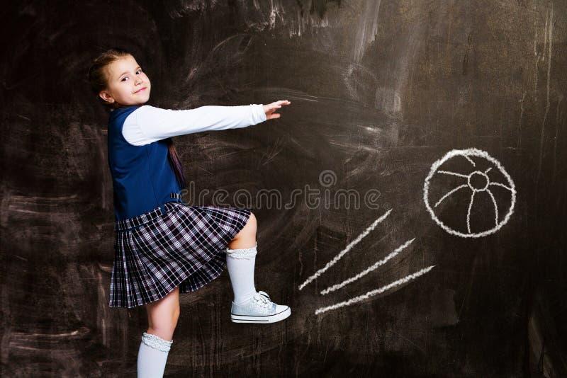 Μαθήτρια ενάντια στον πίνακα κιμωλίας, που κλωτσά μια σφαίρα στοκ εικόνες