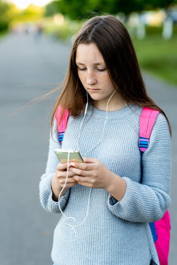 Μαθήτρια κοριτσιών Το καλοκαίρι στην πόλη Χέρια που κρατούν ένα smartphone Γράφει ένα μήνυμα στο διαδίκτυο Στα ακουστικά ακούει στοκ εικόνες