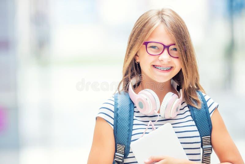 Μαθήτρια με την τσάντα, σακίδιο πλάτης Πορτρέτο του σύγχρονου ευτυχούς σχολικού κοριτσιού εφήβων με τα ακουστικά και την ταμπλέτα στοκ φωτογραφία με δικαίωμα ελεύθερης χρήσης