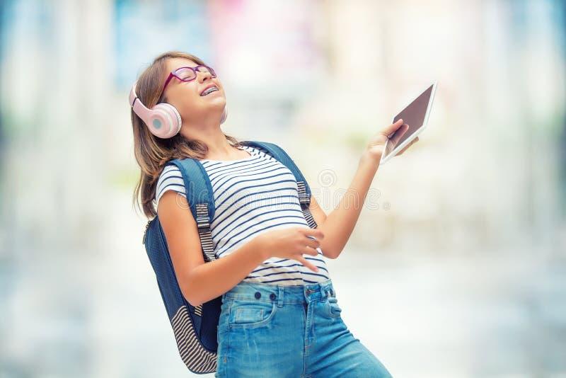 Μαθήτρια με την τσάντα, σακίδιο πλάτης Πορτρέτο του σύγχρονου ευτυχούς σχολικού κοριτσιού εφήβων με τα ακουστικά και την ταμπλέτα στοκ φωτογραφίες