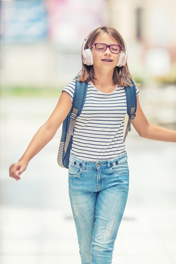 Μαθήτρια με την τσάντα, σακίδιο πλάτης Πορτρέτο του σύγχρονου ευτυχούς σχολικού κοριτσιού εφήβων με τα ακουστικά και την ταμπλέτα στοκ εικόνες