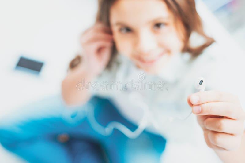 Μαθήτρια που ακούει τα νέα χτυπήματα με τα σύγχρονα ακουστικά στοκ εικόνες με δικαίωμα ελεύθερης χρήσης