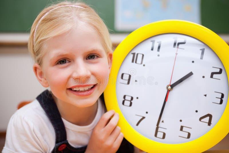 Μαθήτρια που εμφανίζει ένα ρολόι στοκ εικόνα