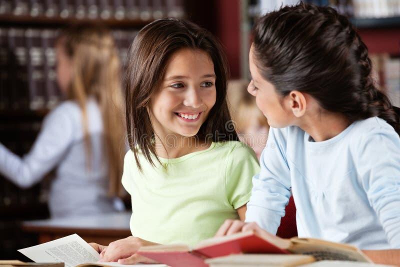 Μαθήτρια που εξετάζει το θηλυκό φίλο στη βιβλιοθήκη στοκ εικόνες