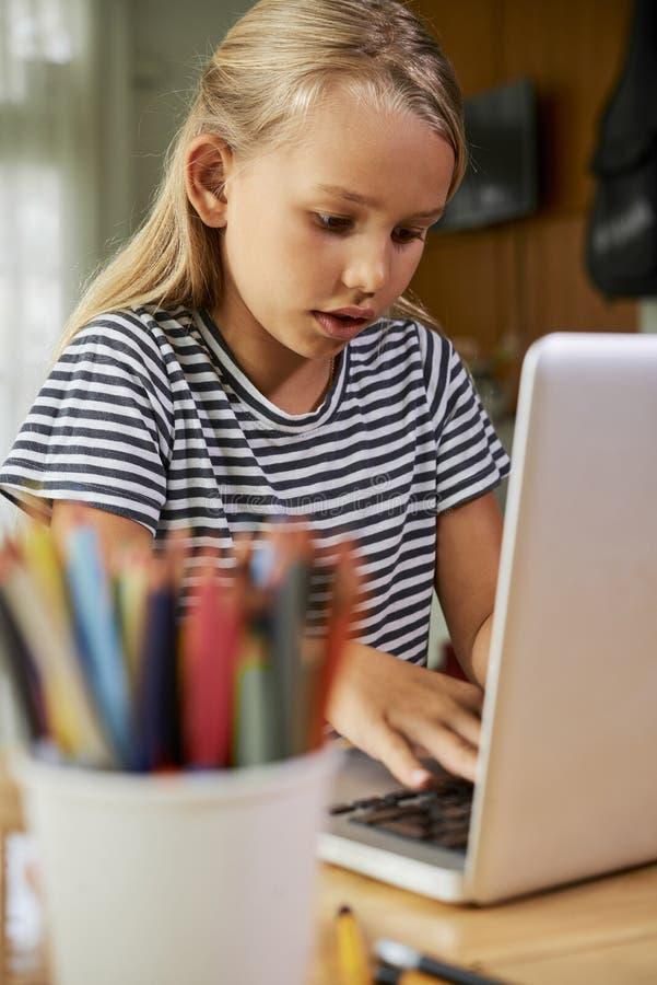 Μαθήτρια που εργάζεται στο lap-top στο σπίτι στοκ φωτογραφίες