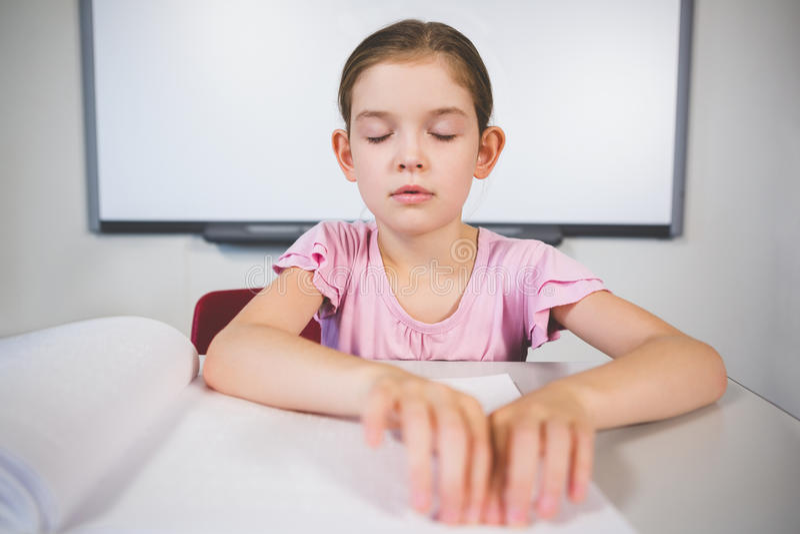 Μαθήτρια που διαβάζει ένα βιβλίο μπράιγ στην τάξη στοκ εικόνα