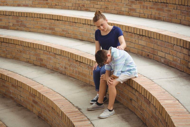 Μαθήτρια που παρηγορεί το λυπημένο φίλο της στα βήματα στην πανεπιστημιούπολη στοκ εικόνα με δικαίωμα ελεύθερης χρήσης