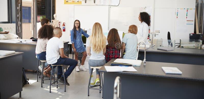 Μαθήτρια που παρουσιάζει το πρόγραμμα μπροστά από την κατηγορία επιστήμης στοκ εικόνες