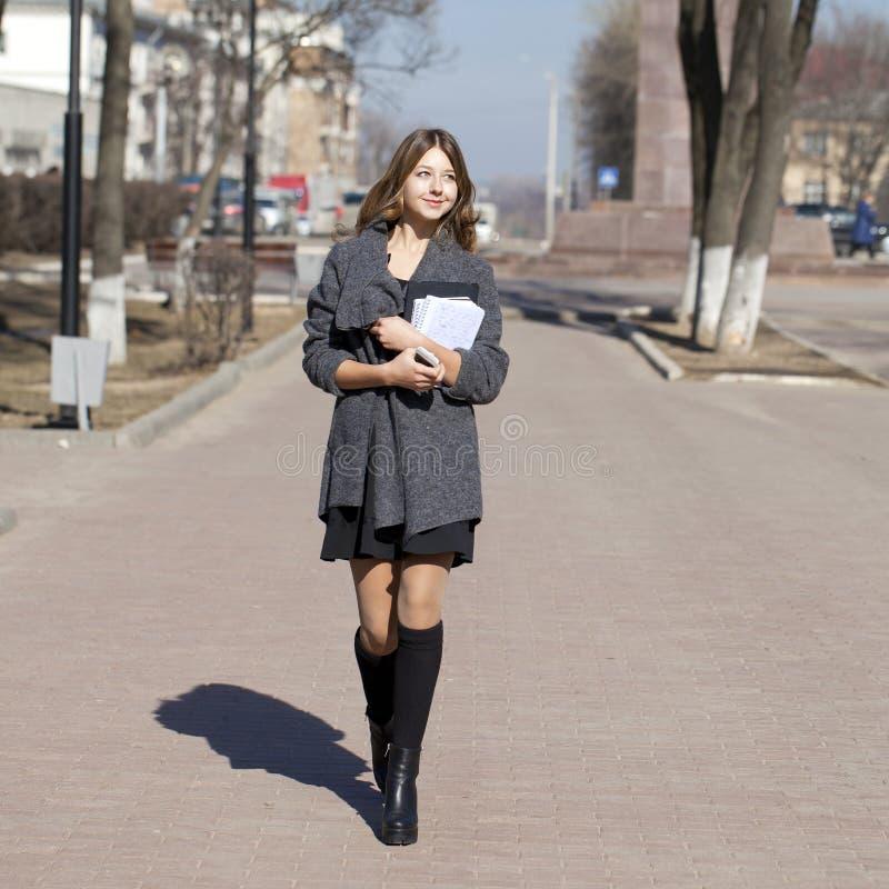 Μαθήτρια που περπατά στην ηλιόλουστη οδό άνοιξη στοκ φωτογραφία με δικαίωμα ελεύθερης χρήσης