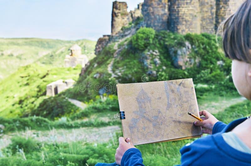 Μαθήτρια που σύρει μια εικόνα του αρχαίου αρμενικού κάστρου Amberd από ένα μολύβι υπαίθρια στοκ φωτογραφία