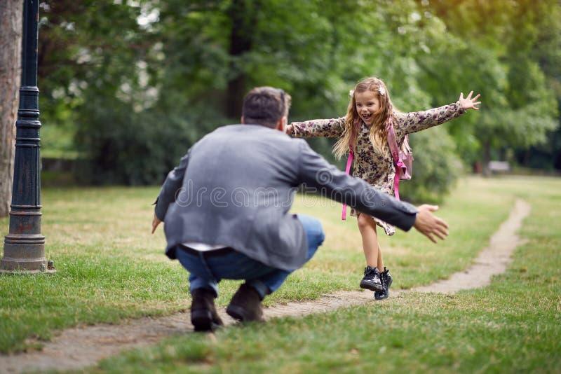 Μαθήτρια που τρέχει στον μπαμπά για να του δώσει ένα αγκάλιασμα στοκ φωτογραφία με δικαίωμα ελεύθερης χρήσης