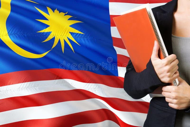 Μαθαίνοντας μαλαισιανή γλωσσική έννοια Νέα γυναίκα που στέκεται με τη σημαία της Μαλαισίας στο υπόβαθρο Βιβλία εκμετάλλευσης δασκ στοκ εικόνα με δικαίωμα ελεύθερης χρήσης