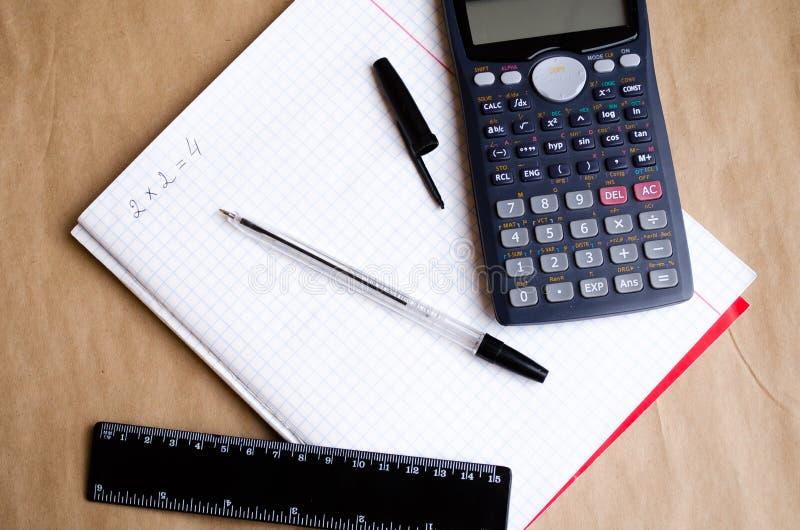 Μαθηματικά Σχολικοί υπολογισμοί Δύο και τέσσερα Σημειωματάριο Bugtery Γραφείο για να εργαστεί στο γραφείο Σχολικές προμήθειες Μάν στοκ εικόνες με δικαίωμα ελεύθερης χρήσης