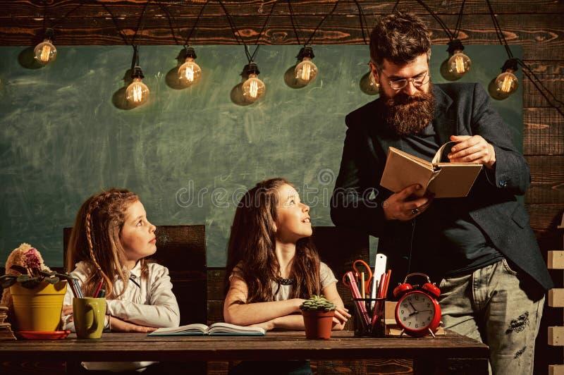 Μαθητές δασκάλων και κοριτσιών στην τάξη, πίνακας κιμωλίας στο υπόβαθρο Περίεργος εύθυμος ακούοντας δάσκαλος παιδιών με στοκ φωτογραφία με δικαίωμα ελεύθερης χρήσης