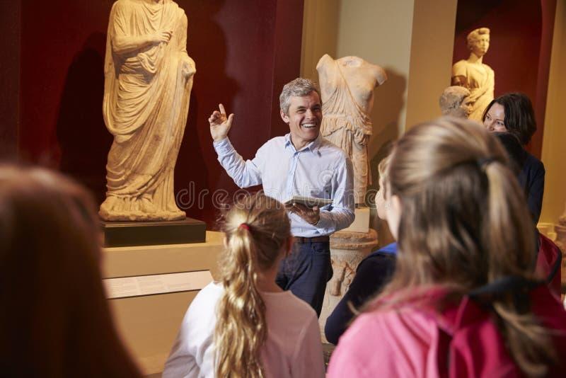 Μαθητές και δάσκαλος στο ταξίδι σχολικών τομέων στο μουσείο με τον οδηγό στοκ φωτογραφία με δικαίωμα ελεύθερης χρήσης