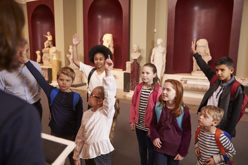 Μαθητές και δάσκαλος στο ταξίδι σχολικών τομέων στο μουσείο με τον οδηγό στοκ φωτογραφίες