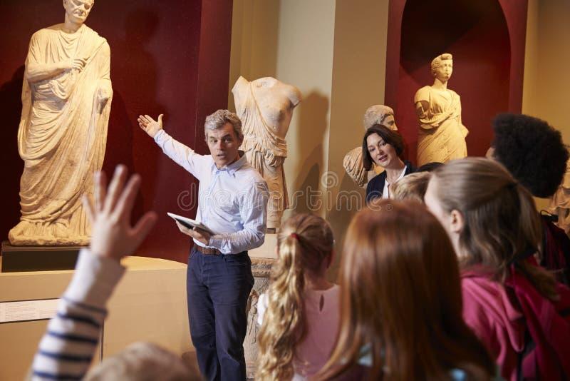 Μαθητές και δάσκαλος στο ταξίδι σχολικών τομέων στο μουσείο με τον οδηγό στοκ εικόνα