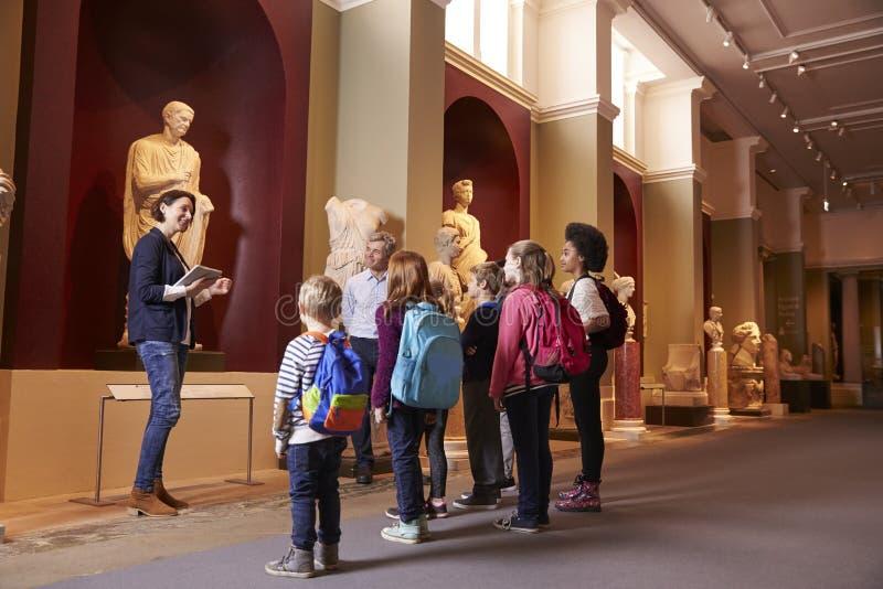 Μαθητές και δάσκαλος στο ταξίδι σχολικών τομέων στο μουσείο με τον οδηγό στοκ φωτογραφία