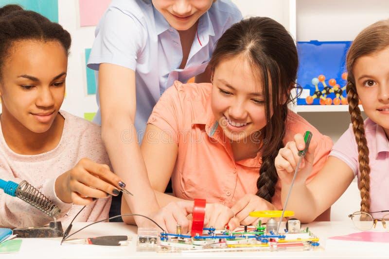 Μαθητές που μαθαίνουν τη φυσική, συγκεντρώνοντας την ηλεκτρική αλυσίδα στοκ φωτογραφία