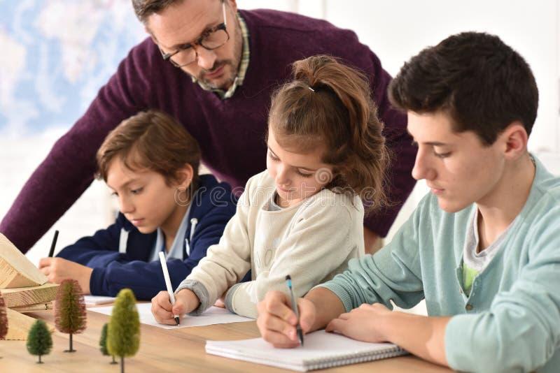 Μαθητές στην κατηγορία με τον καθηγητή στοκ εικόνες