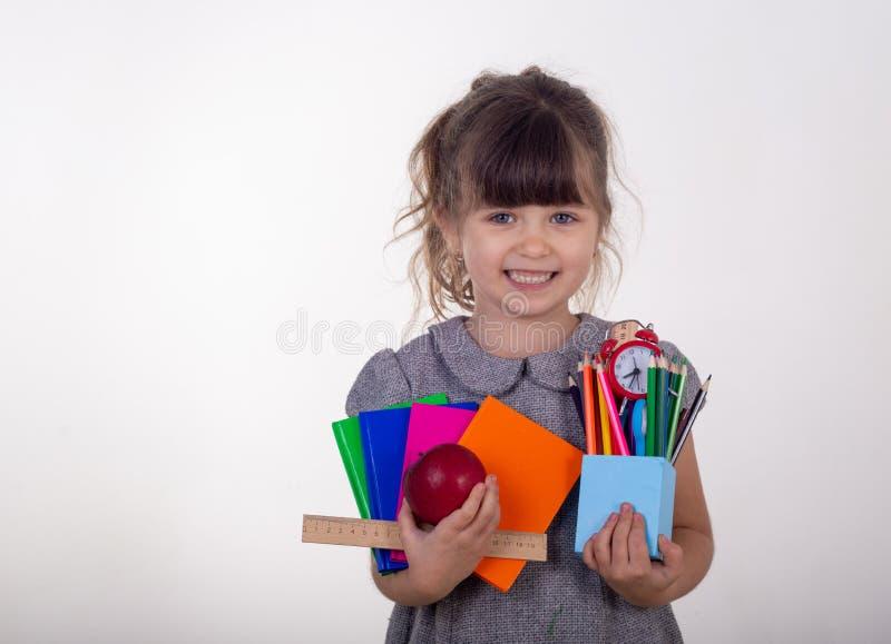 Μαθητής από το δημοτικό σχολείο Σχολικές προμήθειες στα χέρια παιδιών στοκ φωτογραφία