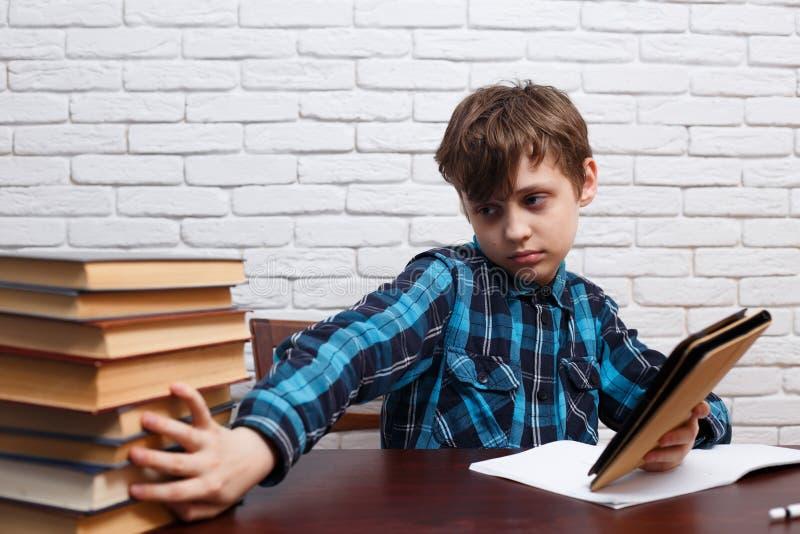 Μαθητής με το ηλεκτρονικό βιβλίο που ωθεί έναν πίσω σωρό των βιβλίων Αριθ. στοκ εικόνες