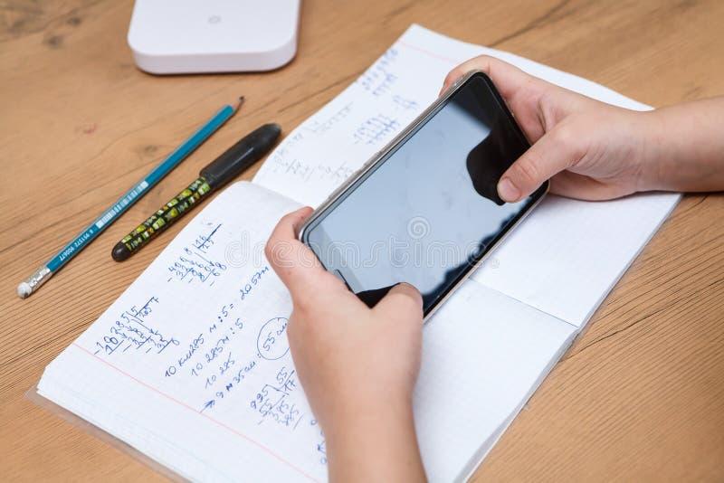 Μαθητής με το smartphone που κάνει την εργασία στο σπίτι στοκ εικόνες