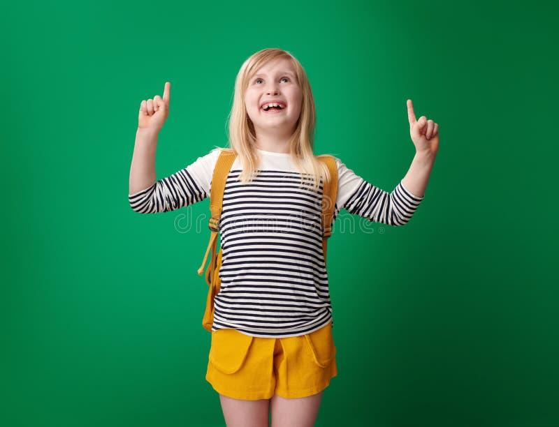 Μαθητής που δείχνει επάνω στο διάστημα αντιγράφων που απομονώνεται στο πράσινο υπόβαθρο στοκ φωτογραφία