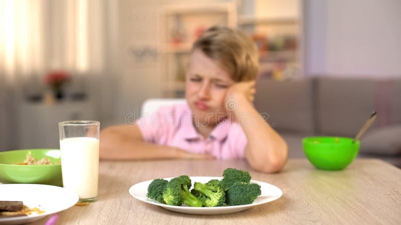Μαθητής που εξετάζει δυστυχώς το μπρόκολο στο άσπρο πιάτο, διατροφή παιδικής ηλικίας, τρόφιμα στοκ φωτογραφία με δικαίωμα ελεύθερης χρήσης