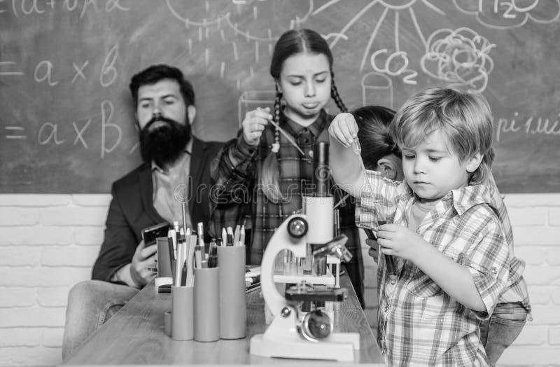Μαθητής που εξετάζει μέσω του μικροσκοπίου το δημοτικό σχολείο πειραματισμός με τις χημικές ουσίες ή μικροσκόπιο στο εργαστήριο στοκ εικόνες