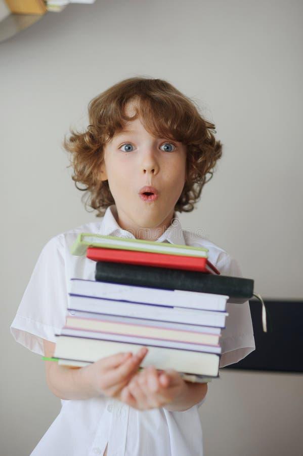 Μαθητής που κρατά έναν σωρό των βιβλίων στοκ φωτογραφίες