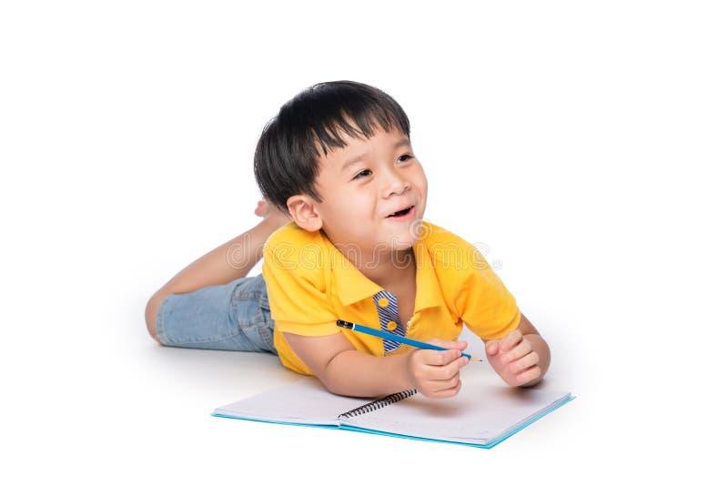 Μαθητής που ξαπλώνει και που γράφει στο σημειωματάριο στοκ εικόνες