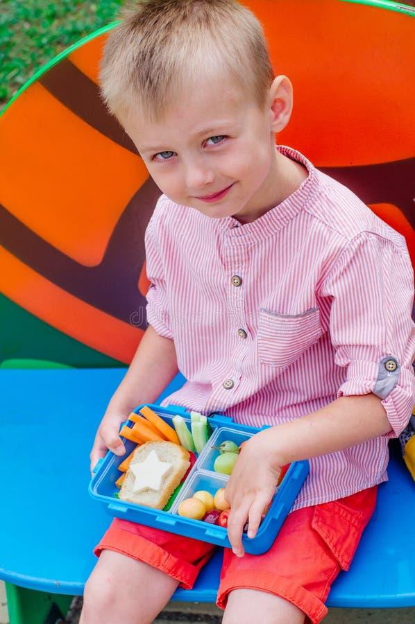 Μαθητής που τρώει το μεσημεριανό γεύμα του από το καλαθάκι με φαγητό υπαίθριο στοκ εικόνα