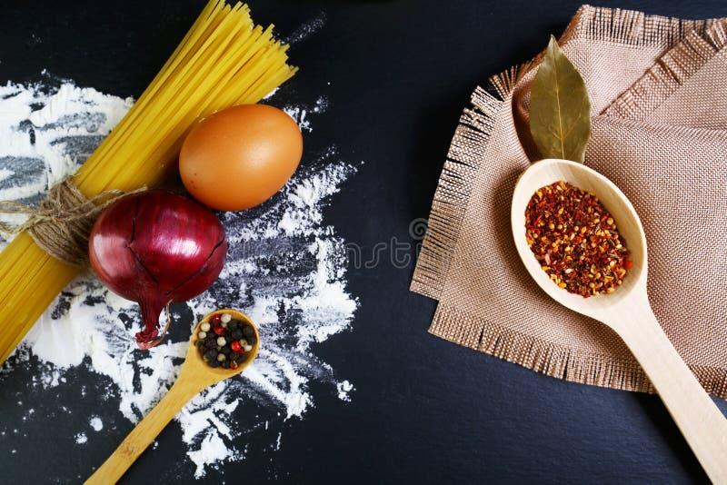 Μακαρόνια ζυμαρικών, ιταλικό έννοια τροφίμων και σχέδιο επιλογών, καρυκεύματα στα ξύλινα κουτάλια, φύλλο κόλπων κρεμμυδιών, ακατέ στοκ φωτογραφία με δικαίωμα ελεύθερης χρήσης