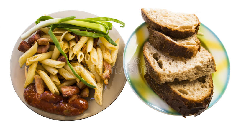Μακαρόνια, τηγανισμένο λουκάνικο, σάλτσα, πράσινα κρεμμύδια με το ψωμί στοκ εικόνες